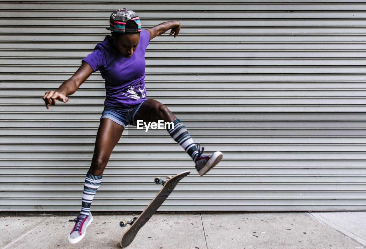 Full length of woman skateboarding against shutter