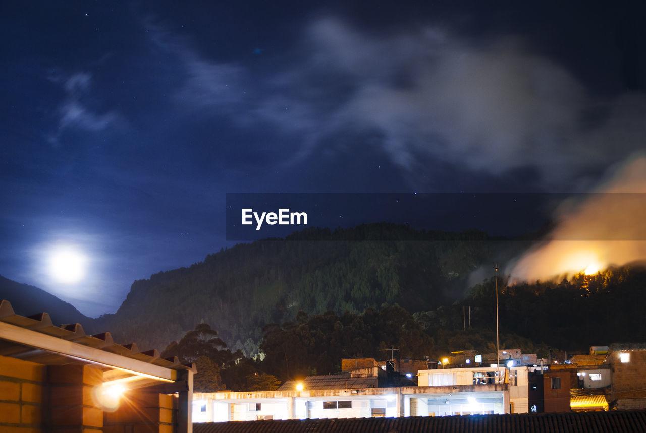 VIEW OF ILLUMINATED MOUNTAINS AT NIGHT