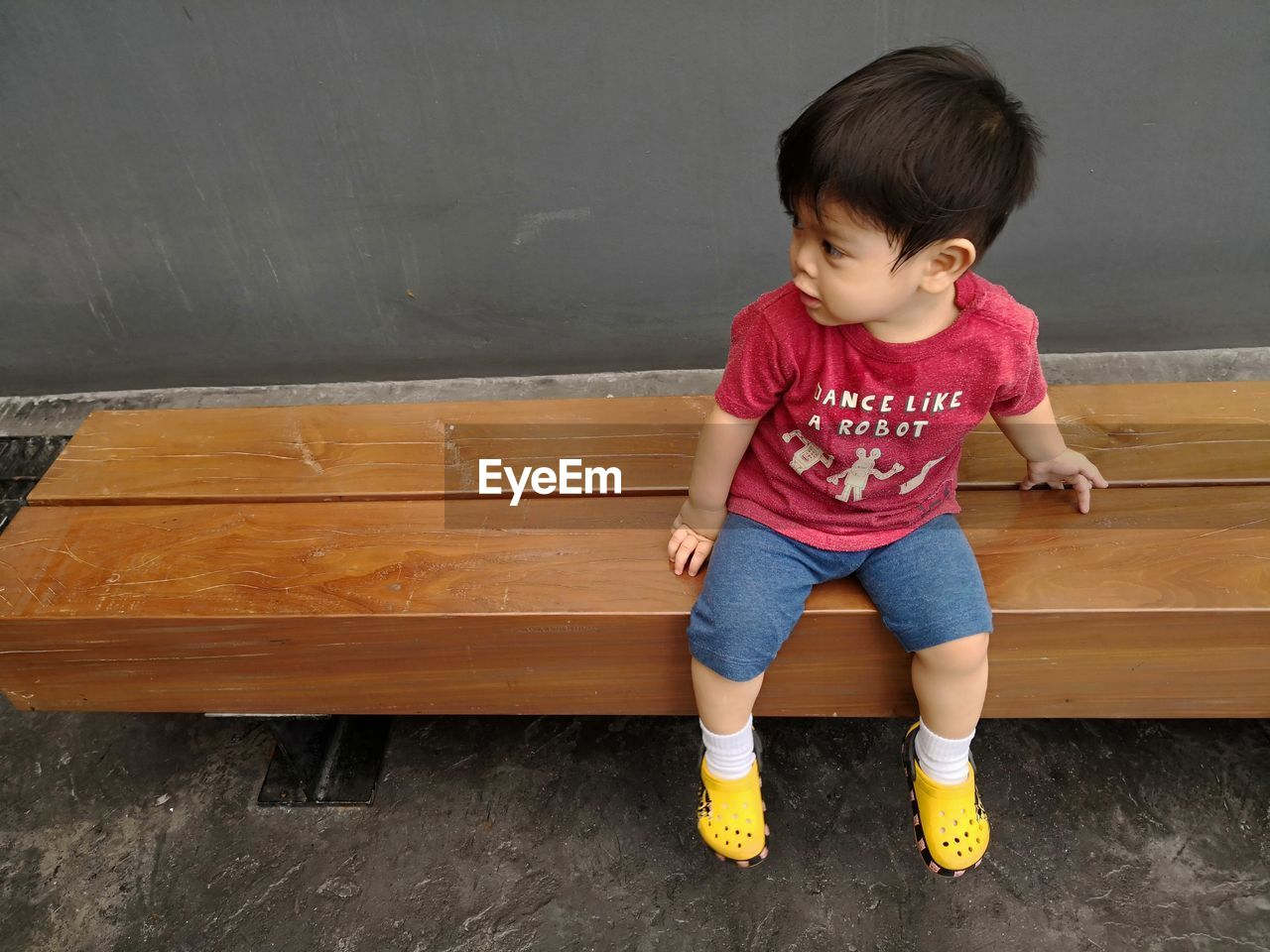 Full length of cute boy looking away while sitting on bench against wall