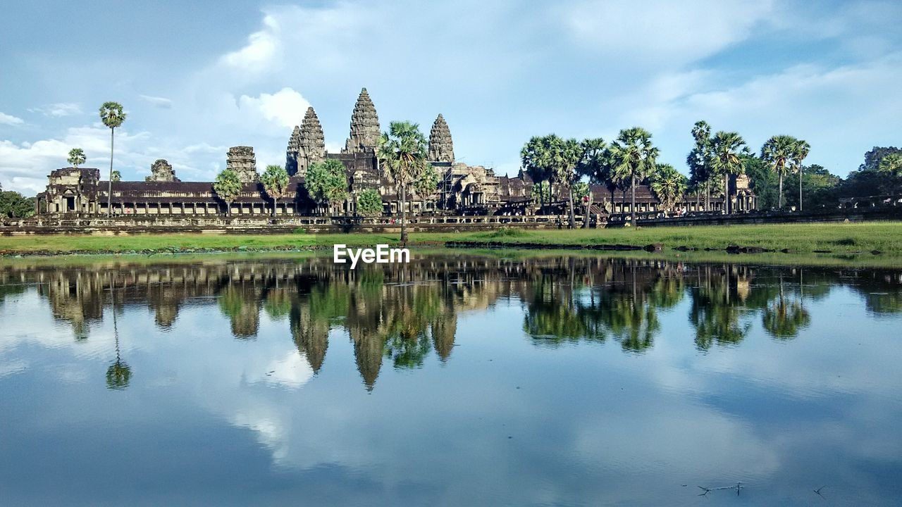 Ancient Angkor Wat Temple Reflection In Lake Against Sky