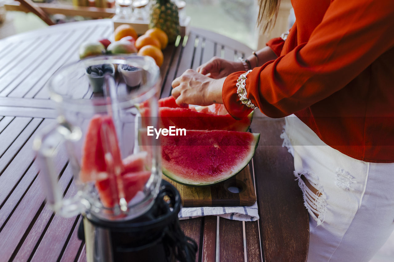food and drink, food, real people, freshness, fruit, healthy eating, red, one person, midsection, preparation, wellbeing, holding, standing, kitchen, women, kitchen utensil, slice, indoors, lifestyles, hand, preparing food, chef