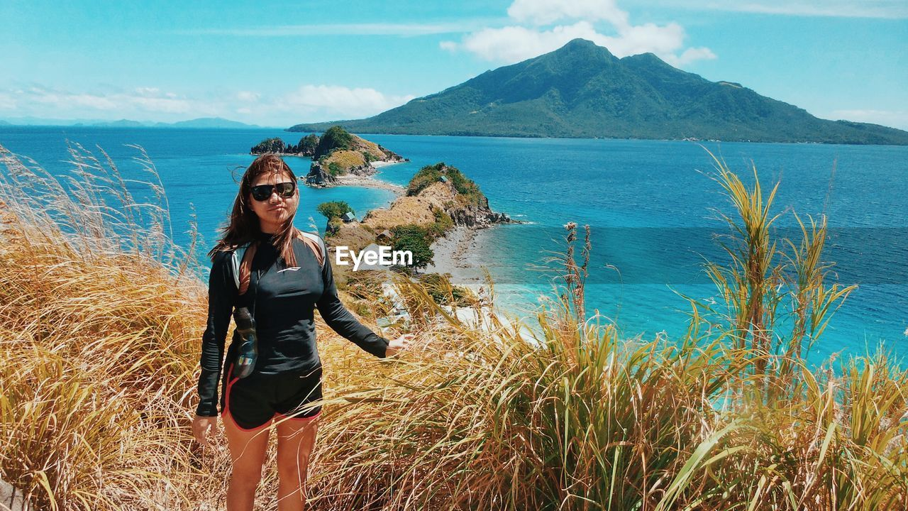 Young woman standing on grassy hill by sea at sambauan island