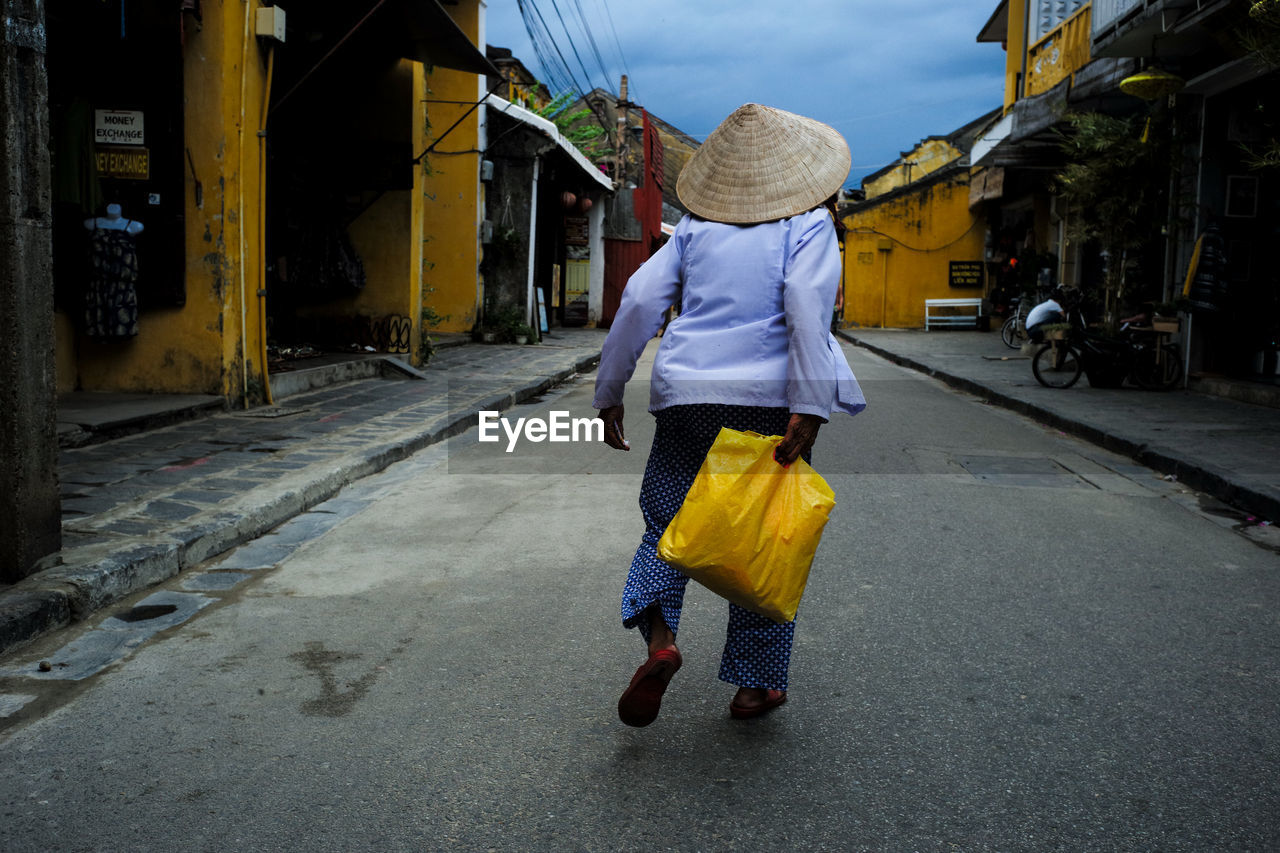 Rear View Of Person Wearing Asian Style Conical Hat While Walking On Road