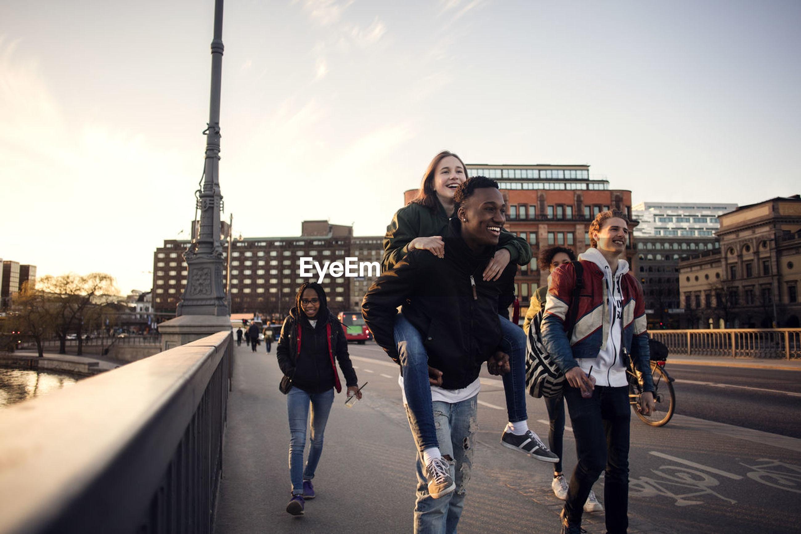 Happy teenage boy piggybacking friend while walking on bridge in city