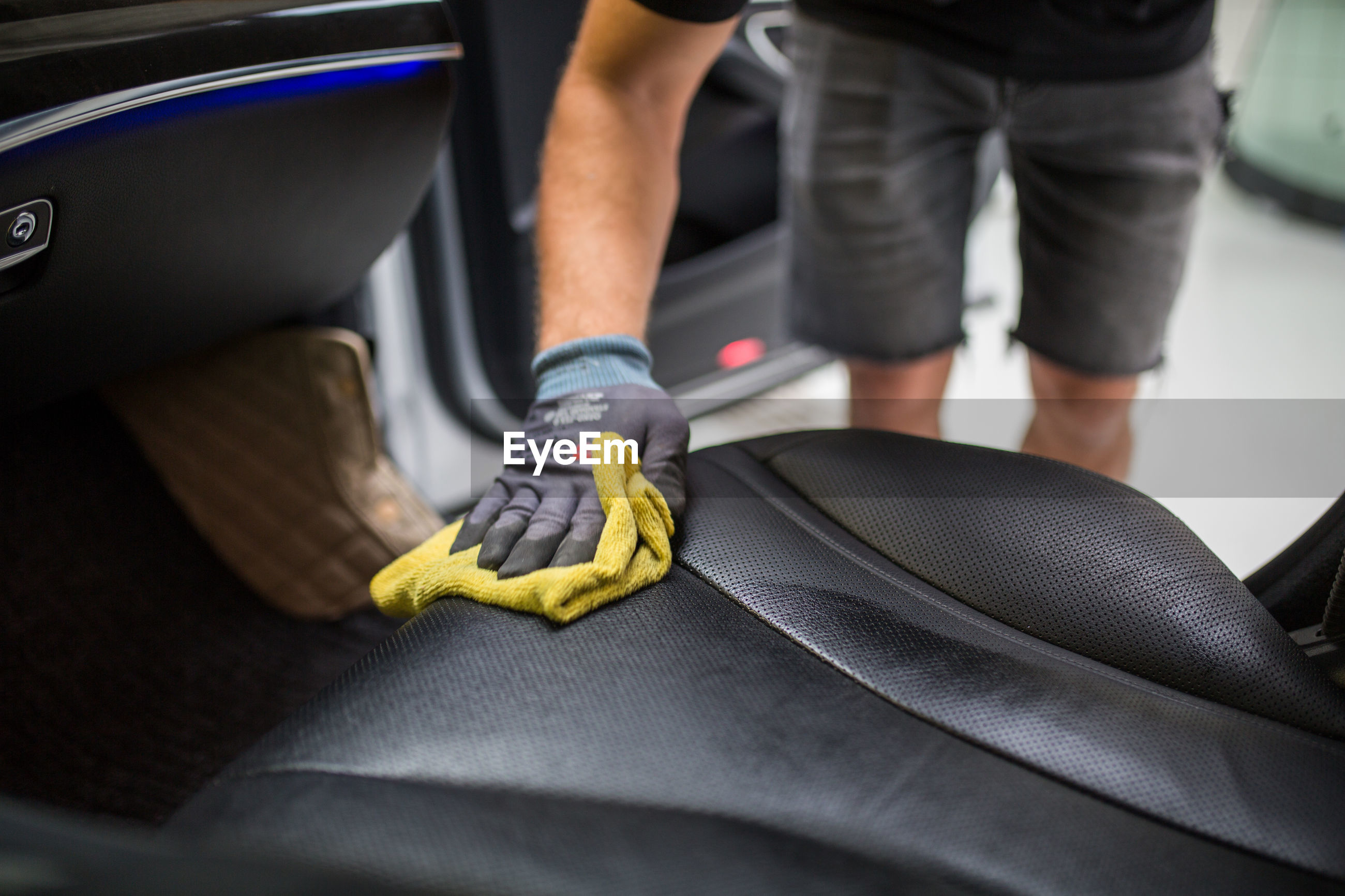 Midsection of man cleaning car seat