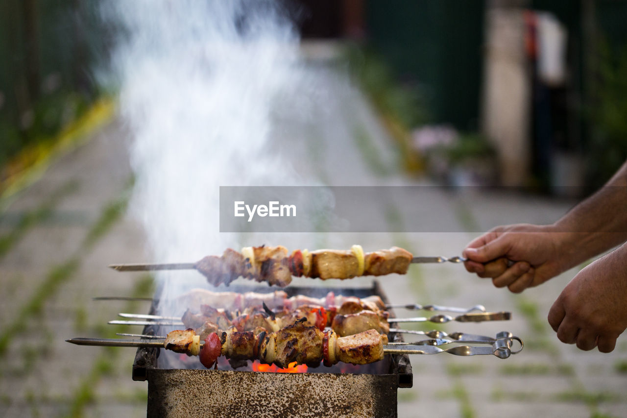 Cropped Image Of Hands Preparing Food On Barbecue Grill In Back Yard
