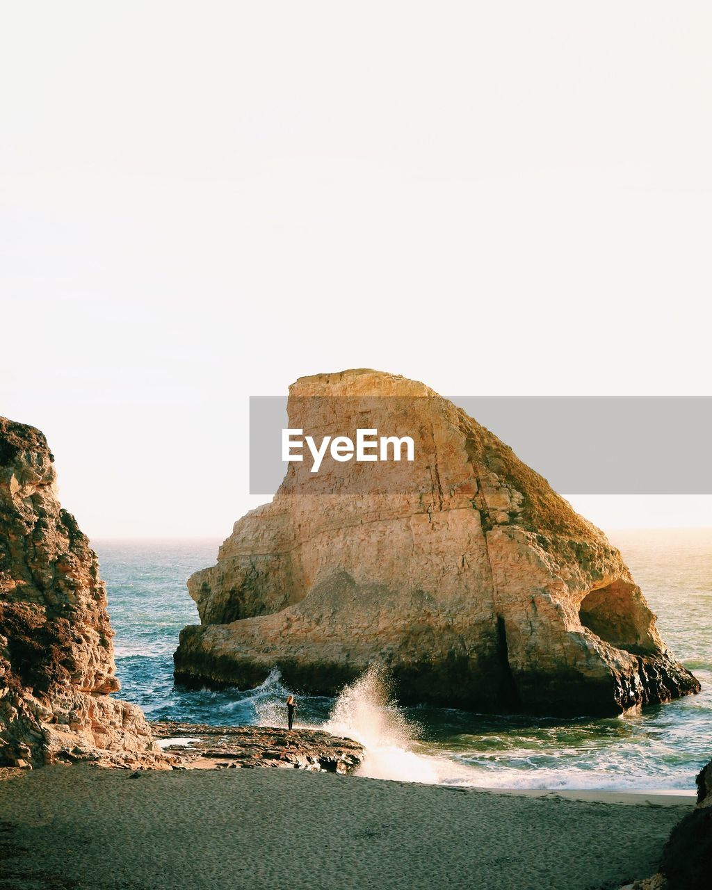 Scenic View Of Large Rock Formation At Beach Against Clear Sky
