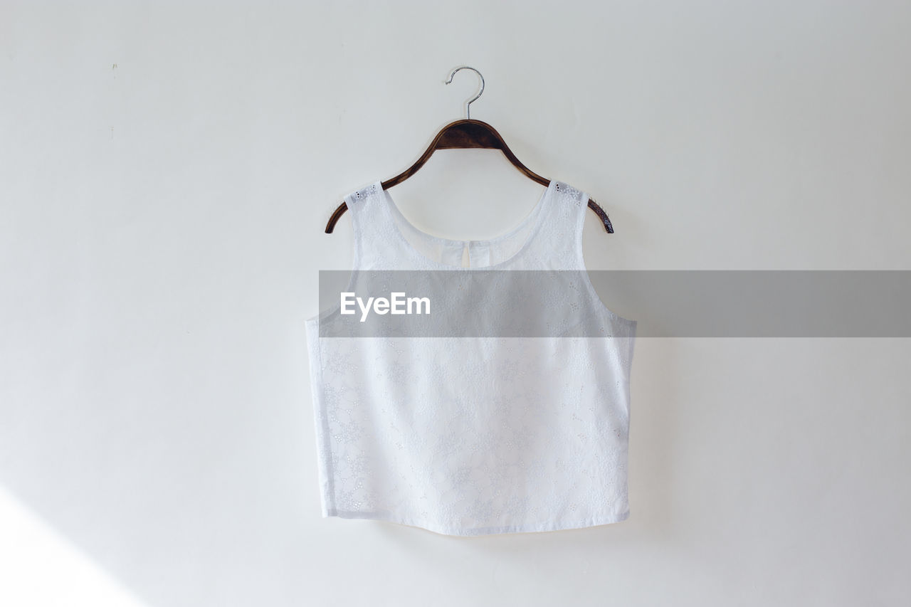 white color, hanging, no people, coathanger, white background, indoors, clothing, studio shot, copy space, fashion, wall - building feature, absence, close-up, white, textile, still life, t-shirt, single object, simplicity, cut out, clean