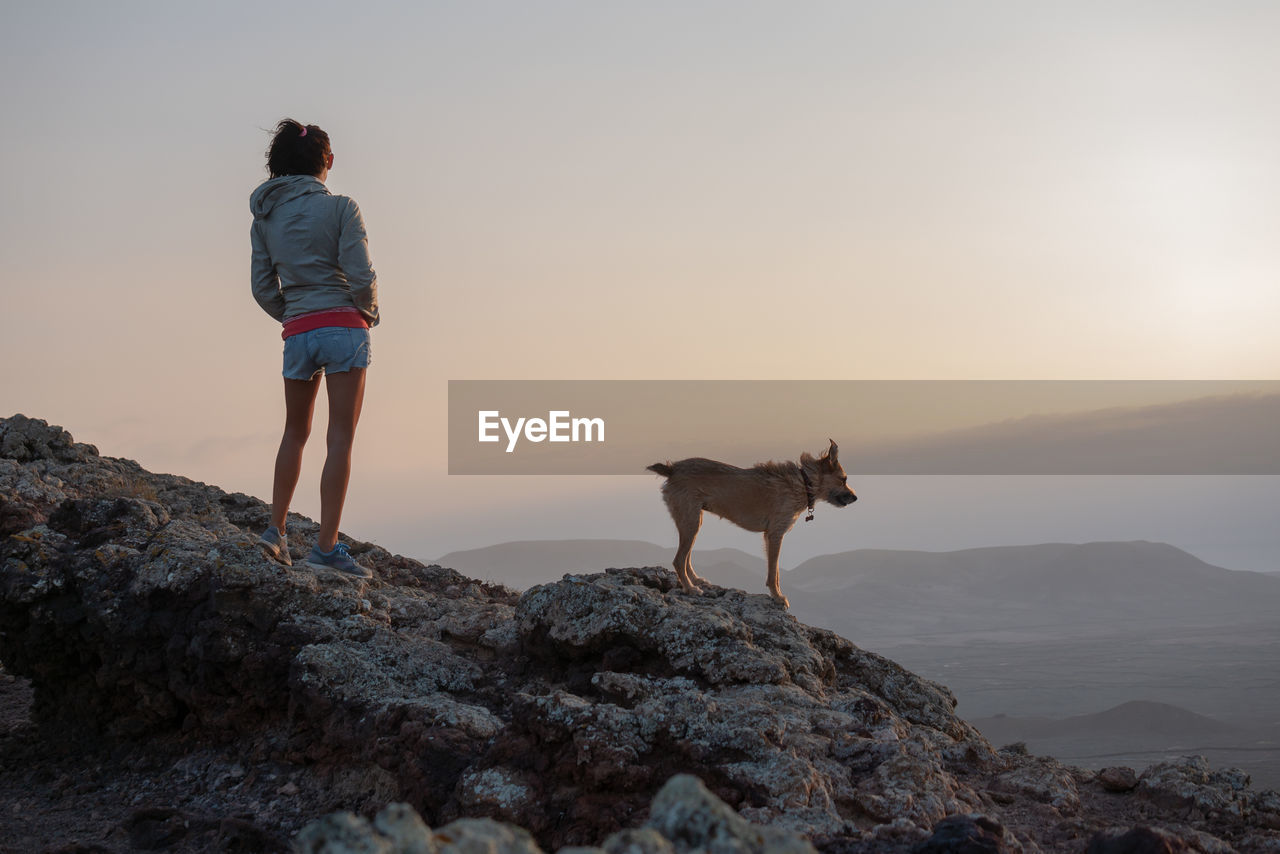 Rear View Of Woman With Dog Standing On Cliff Against Sky During Sunset