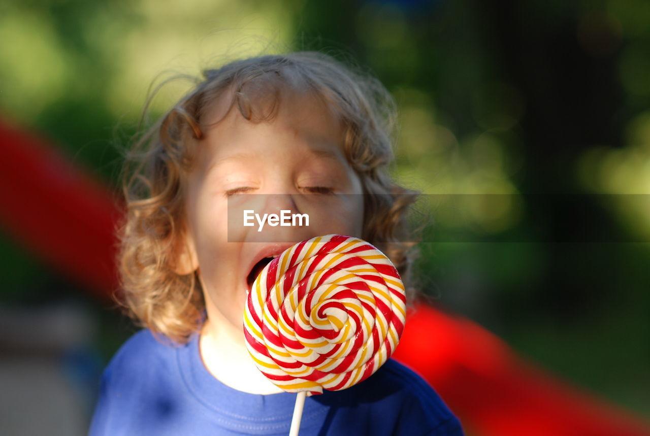 Close-Up Of Cute Boy Eating Lollipop