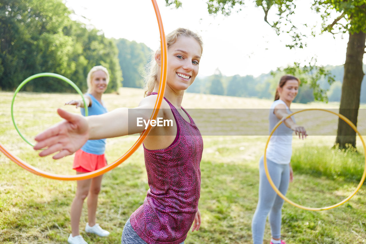 Portrait of smiling woman with plastic hoops standing on field in park