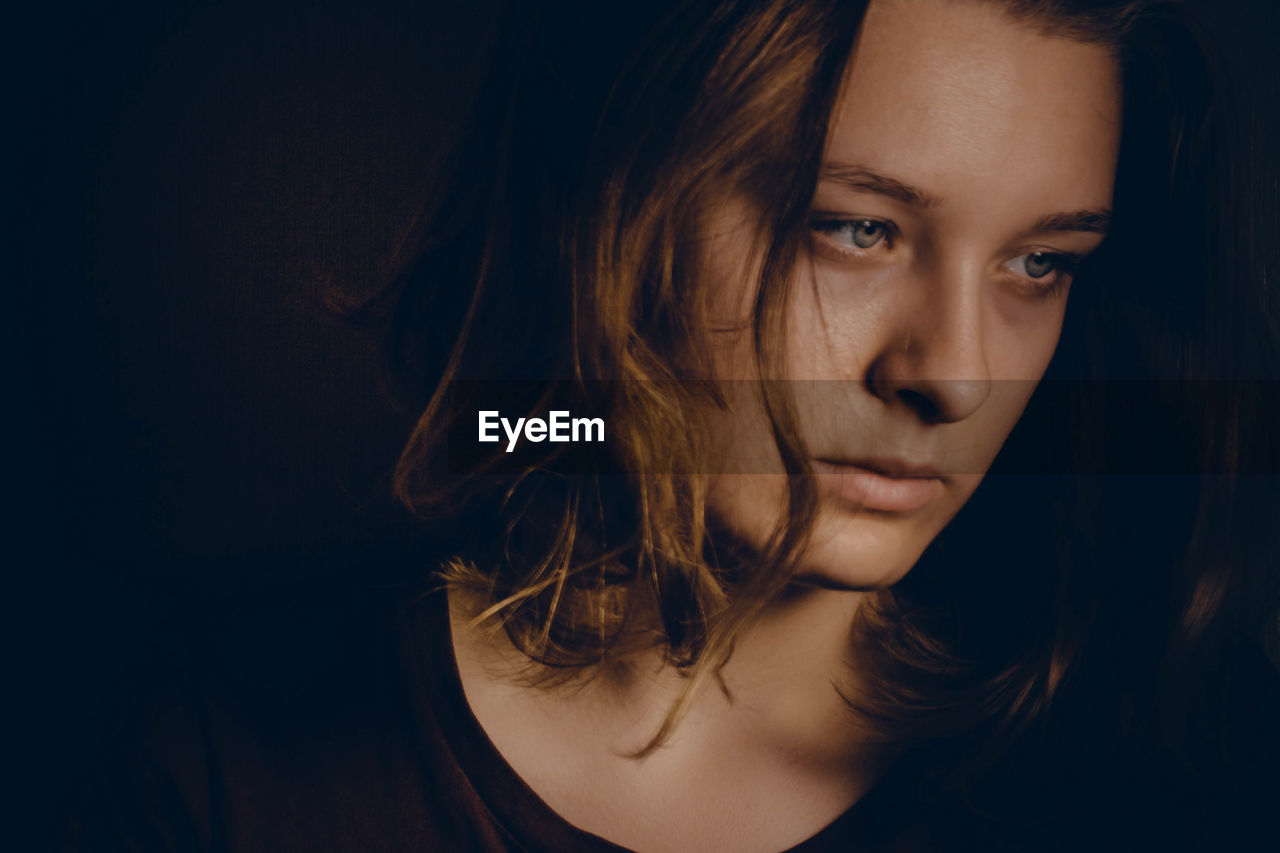 Close-Up Of Sad Young Woman Against Black Background