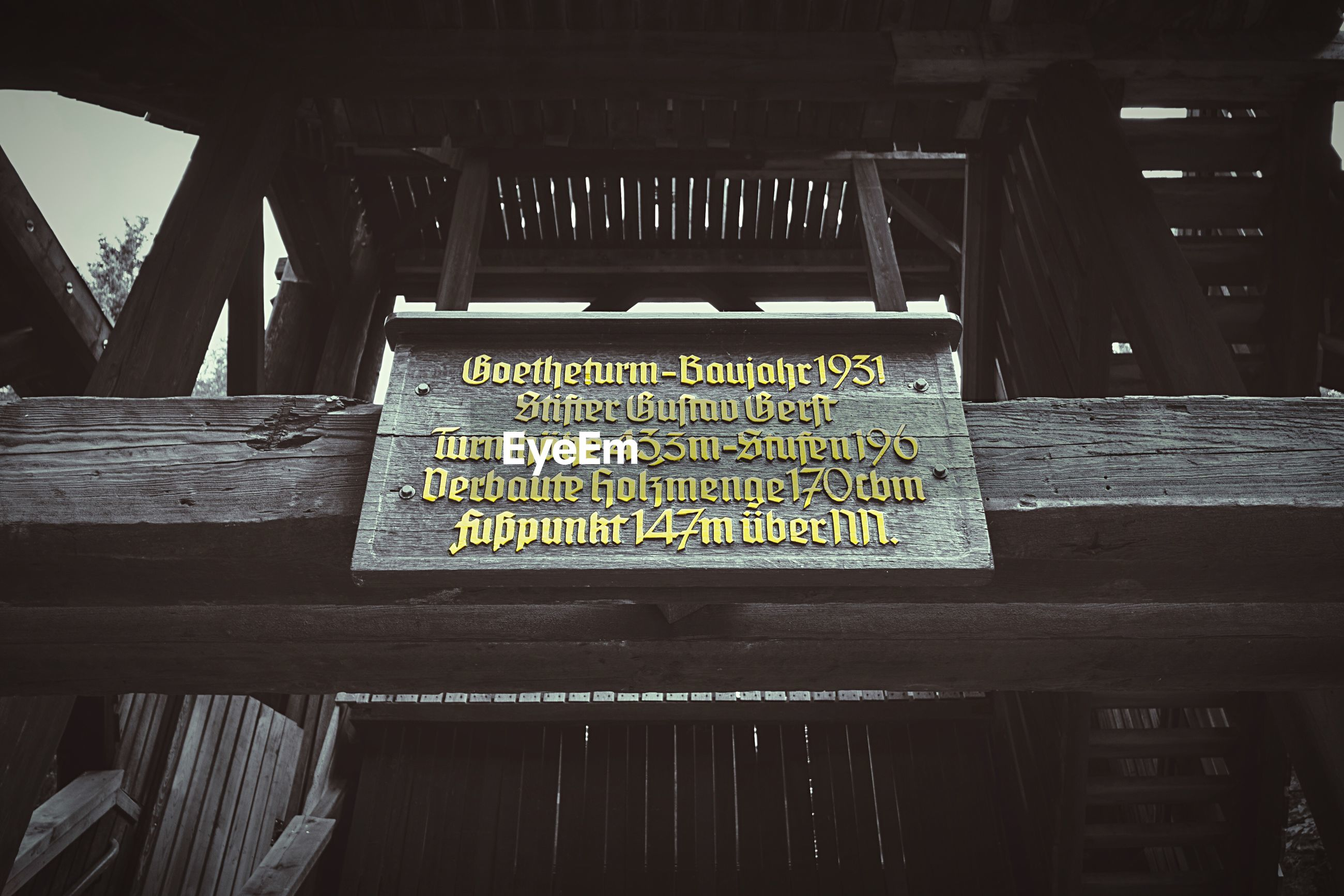 LOW ANGLE VIEW OF TEXT ON WOODEN STRUCTURE