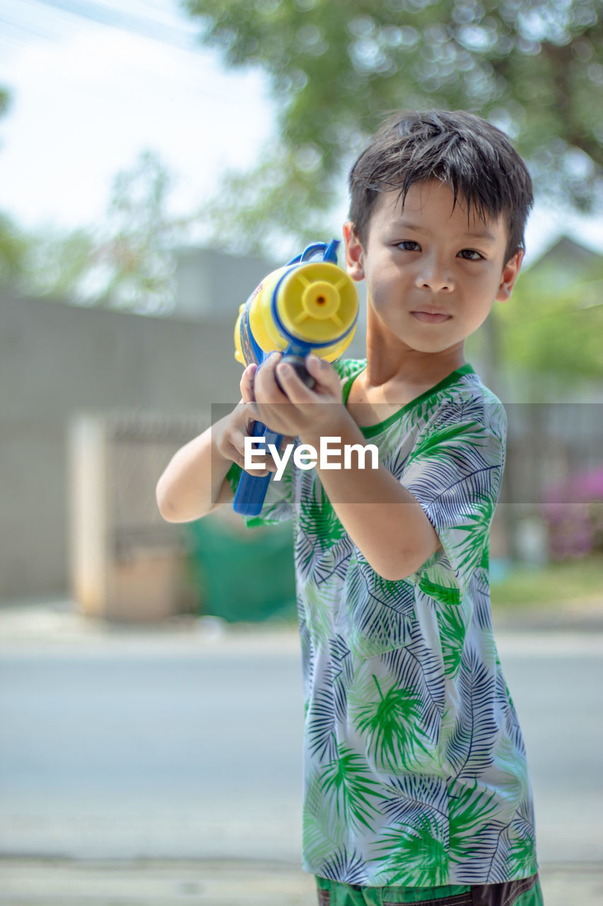 Portrait of cute boy holding squirt gun while standing outdoors