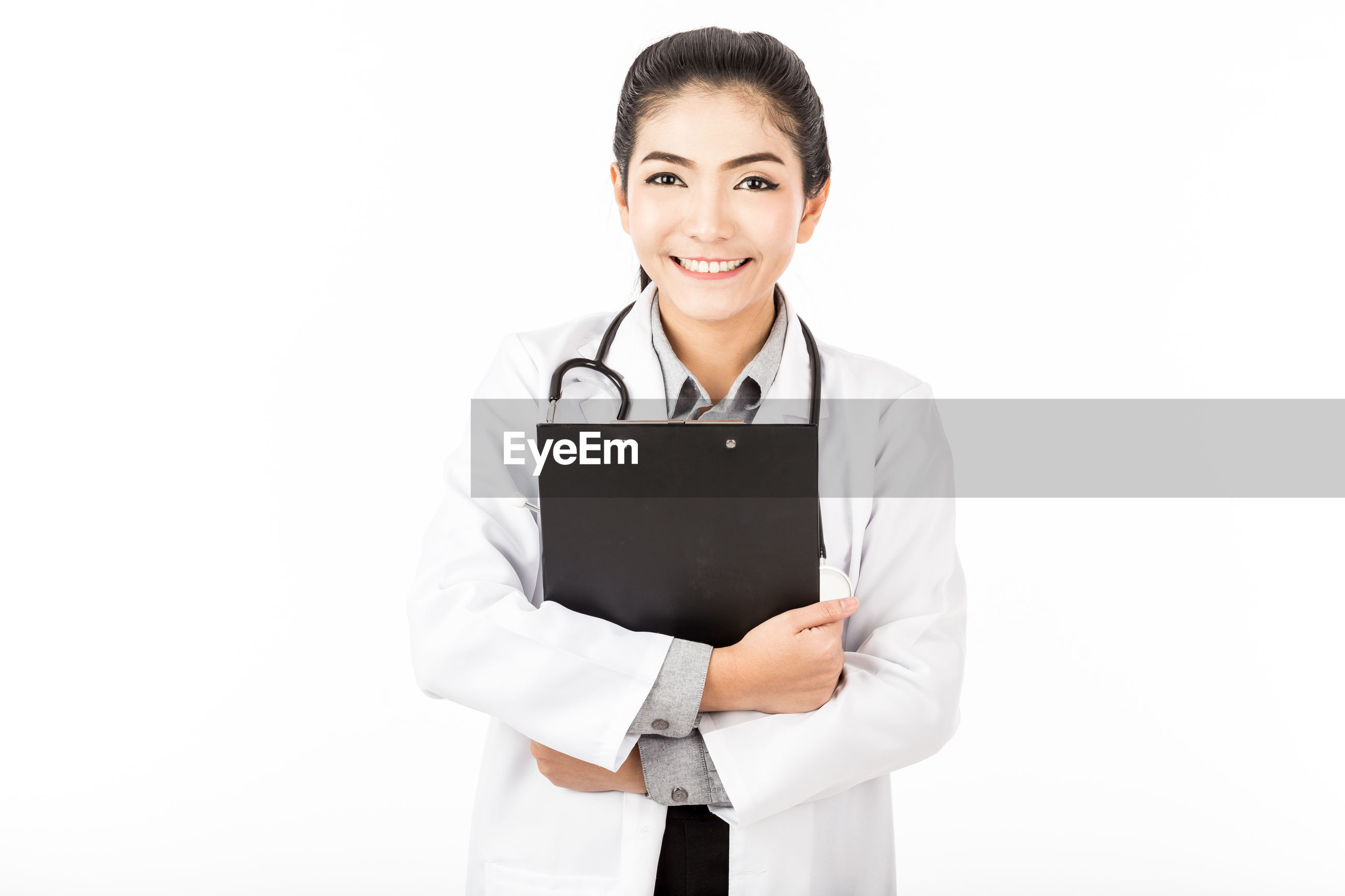 Portrait of smiling female doctor holding clipboard while standing against white background