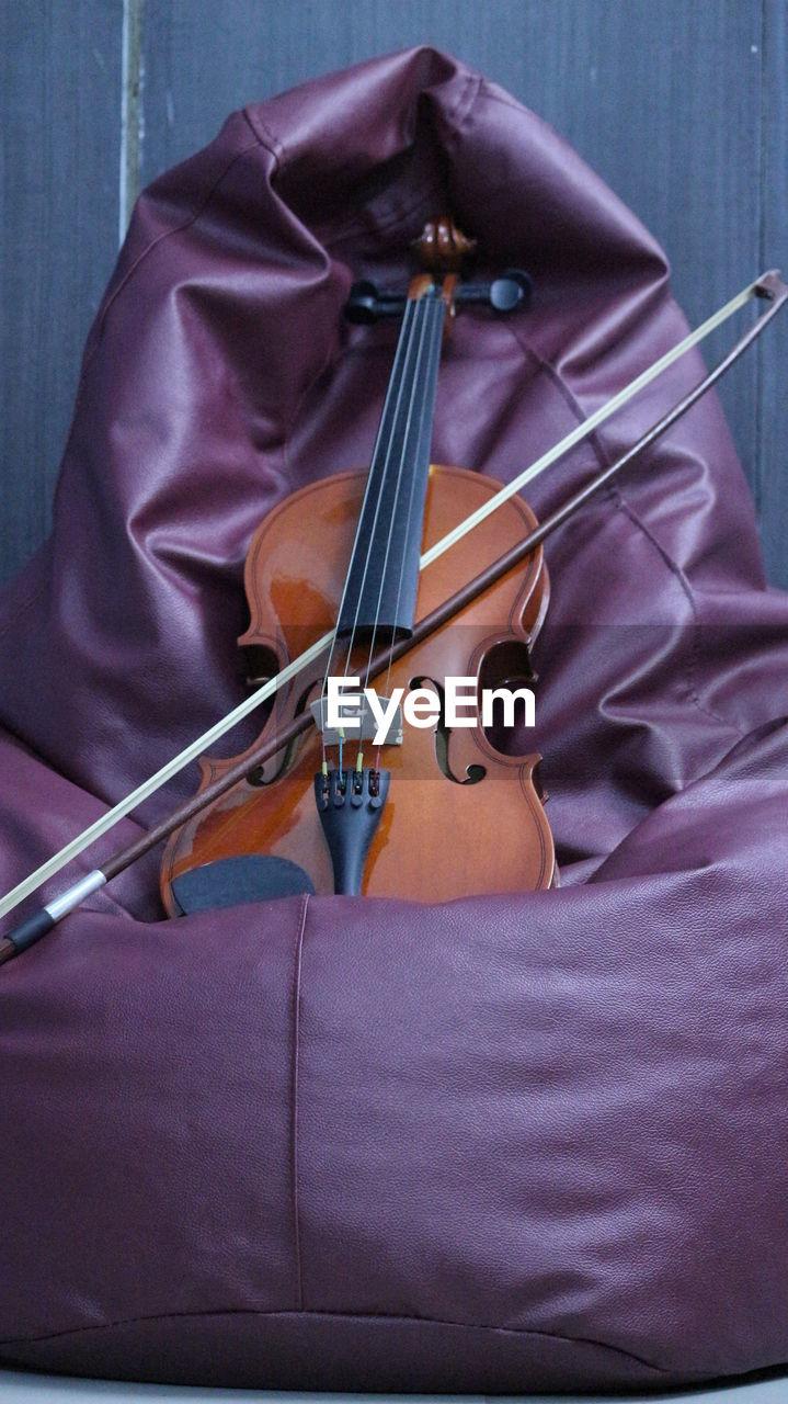 Violin Over Bean Bag Against Wall