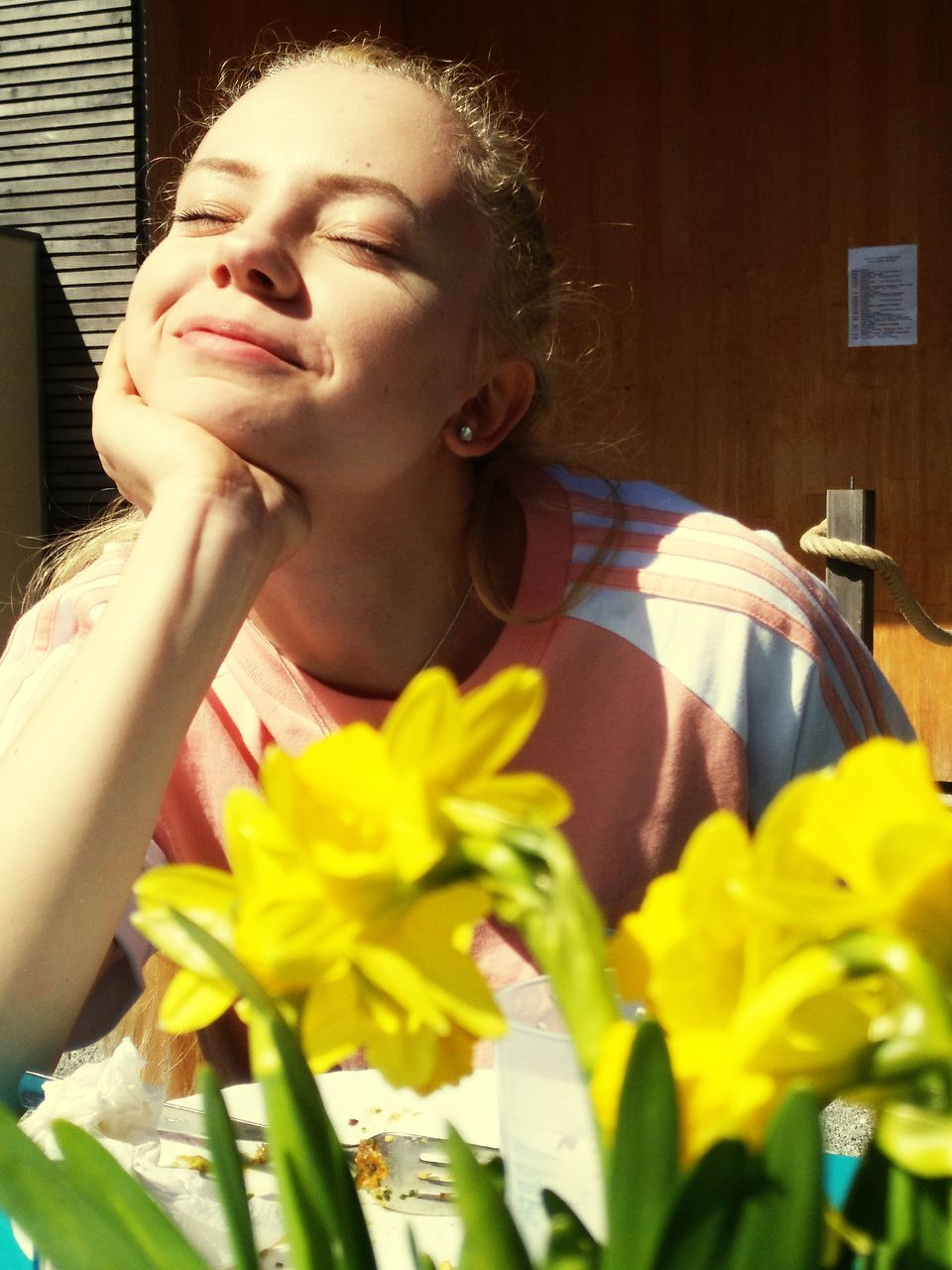 Smiling Woman With Yellow Flowers In Cafe