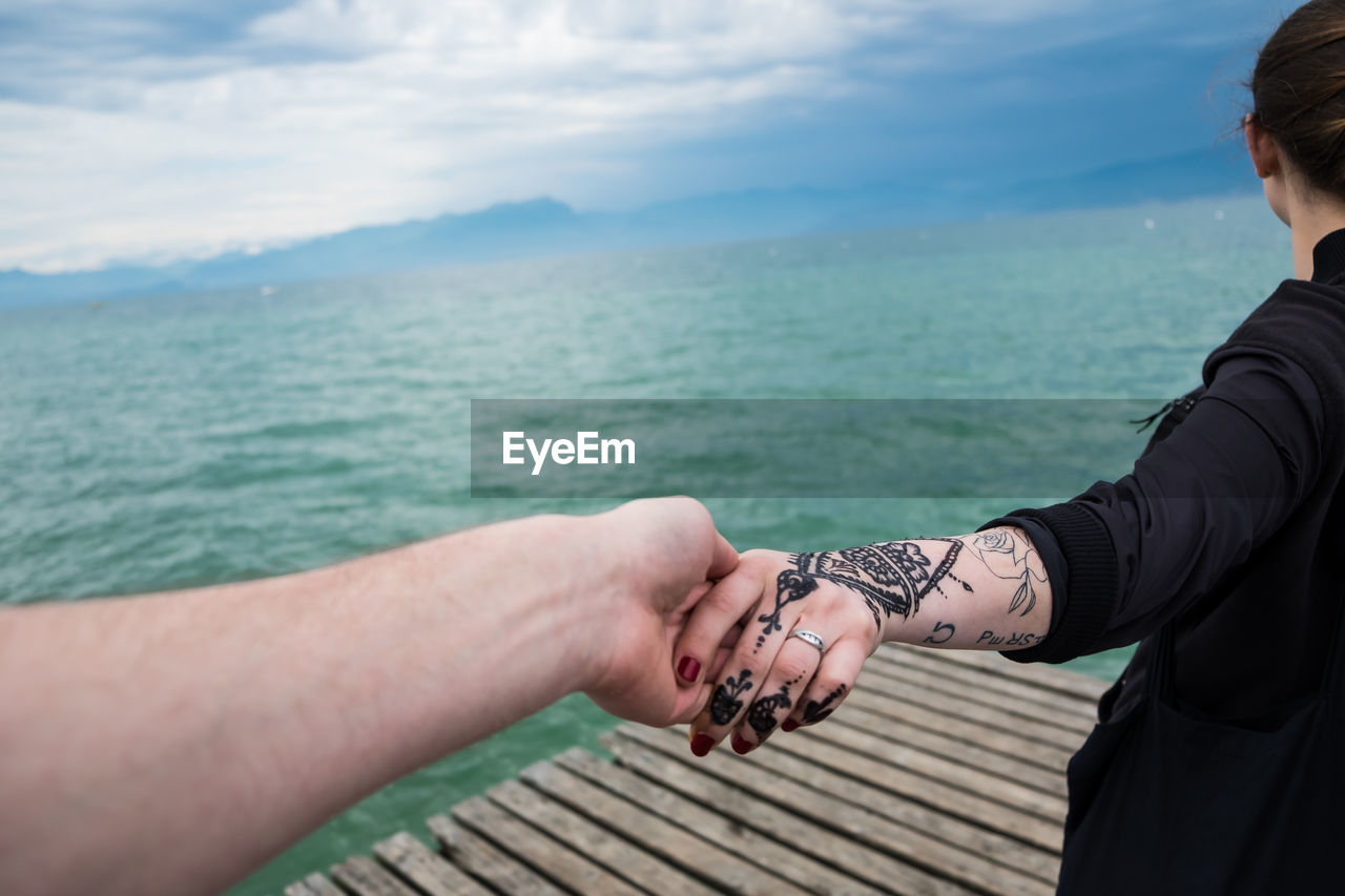 Cropped image of man holding woman hand with henna tattoo at peschiera del garda