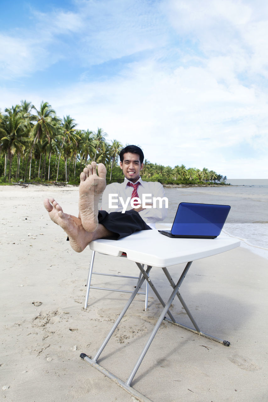 full length, young adult, sitting, sky, one person, young men, front view, real people, chair, nature, land, cloud - sky, beach, day, tree, seat, laptop, plant, wireless technology, outdoors, using laptop