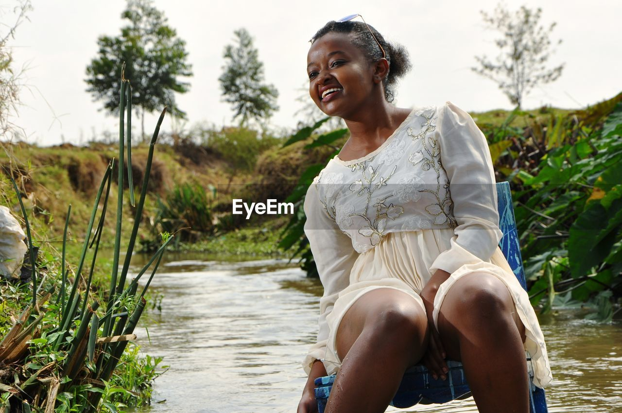 Young Woman Sitting On Chair Against Stream Against Sky