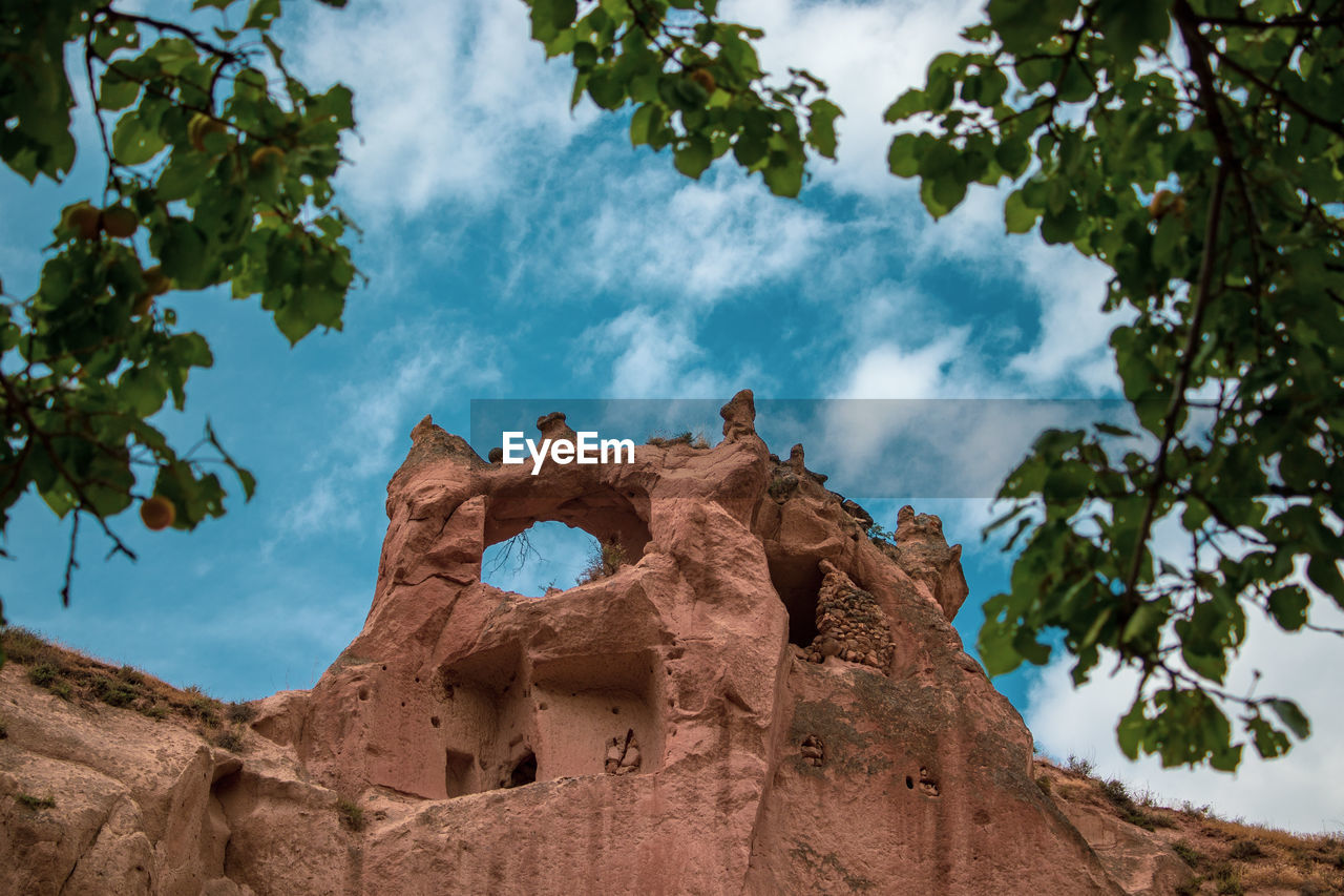 sky, low angle view, cloud - sky, tree, plant, nature, day, no people, outdoors, beauty in nature, travel, travel destinations, sunlight, tranquility, rock formation, history, architecture, rock, blue, the past, eroded