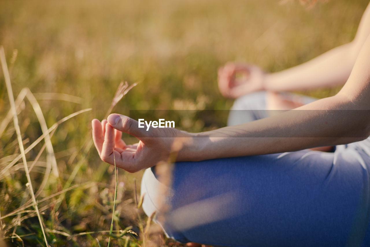 Woman Meditating On Field