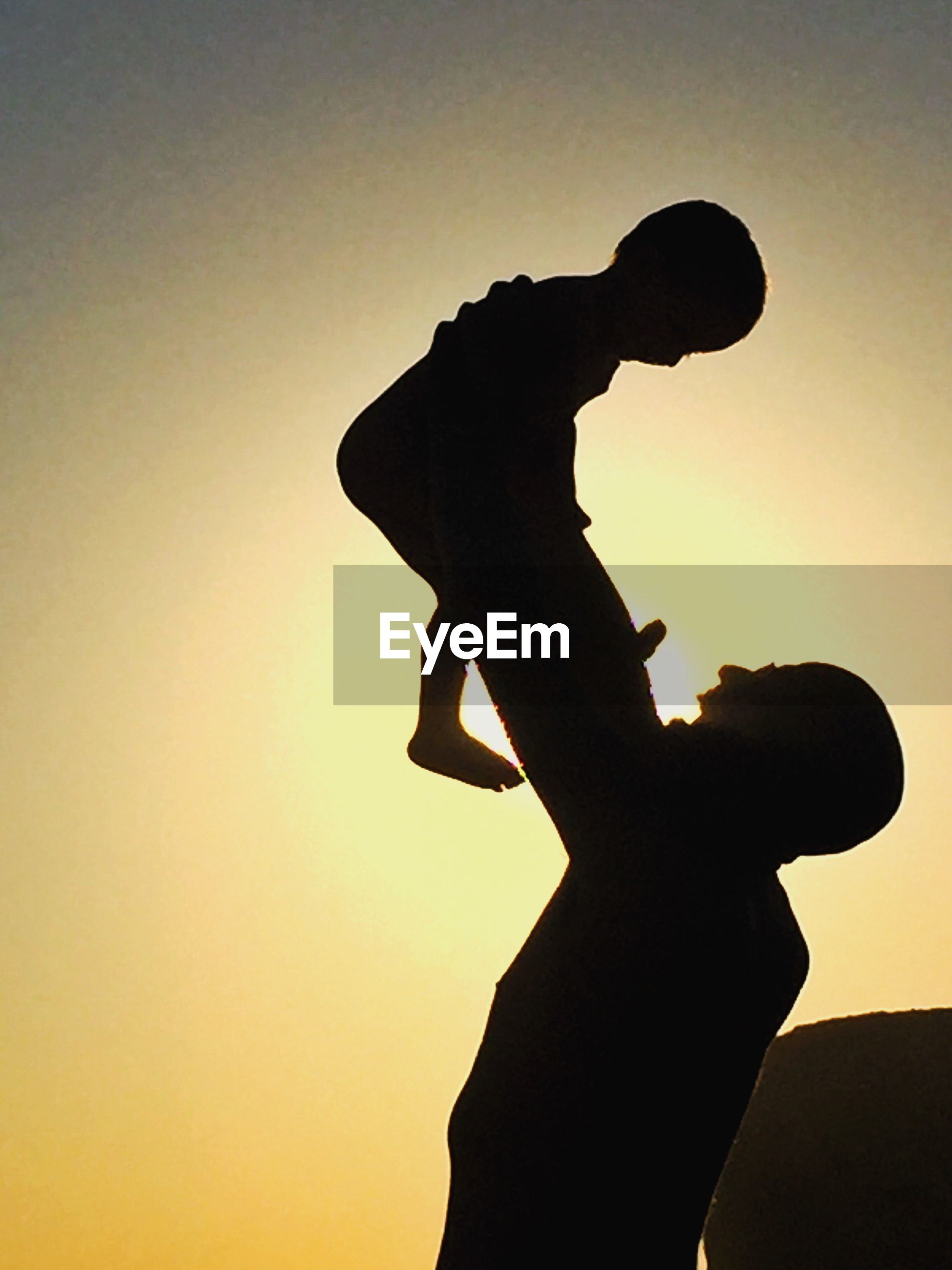 Silhouette father holding baby against sky during sunset