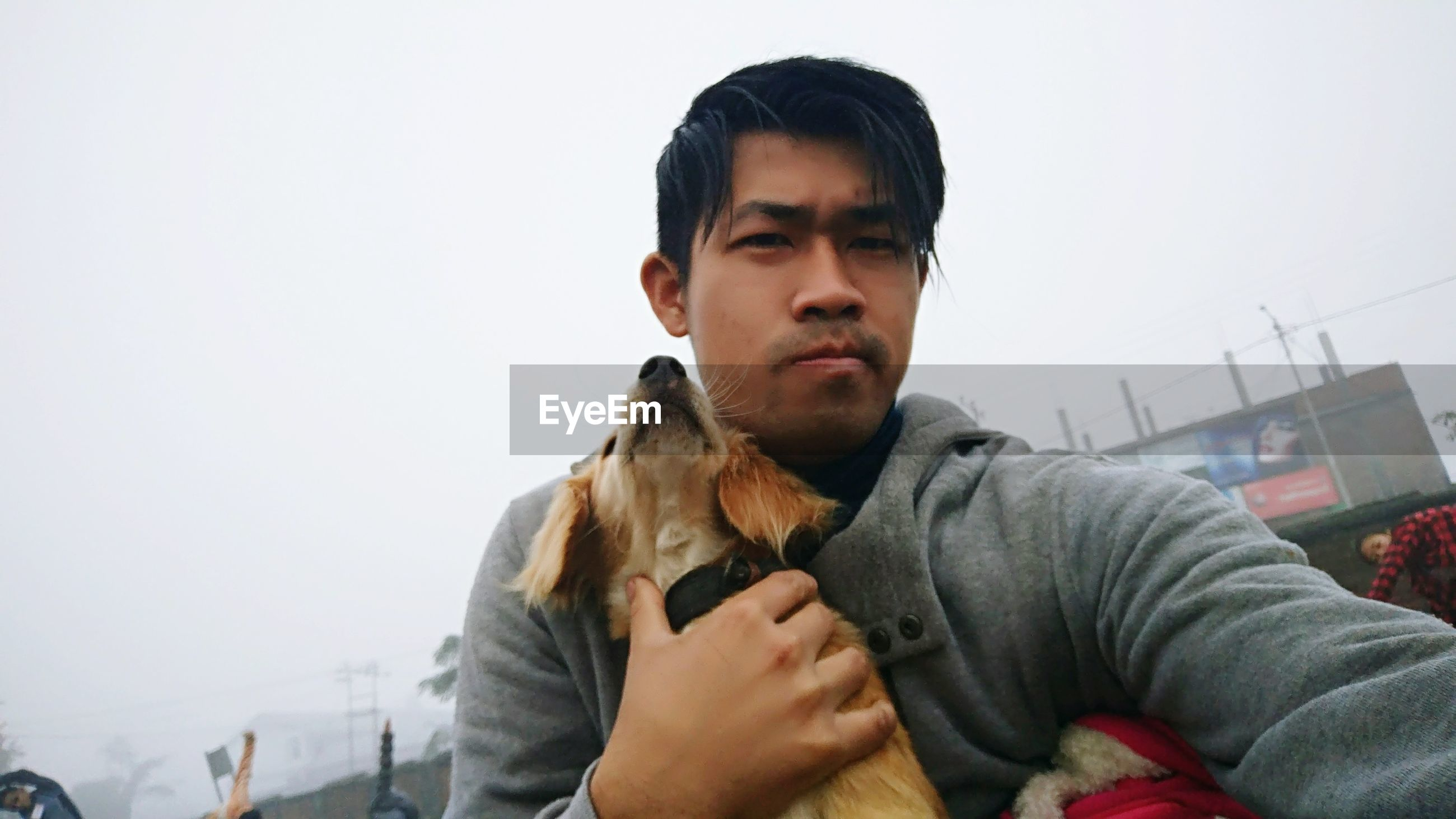 Portrait of young man holding dog against clear sky