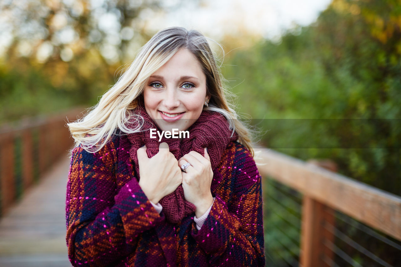 portrait, looking at camera, warm clothing, hair, smiling, one person, blond hair, clothing, women, real people, winter, young adult, focus on foreground, young women, scarf, happiness, beautiful woman, leisure activity, waist up, hairstyle, outdoors