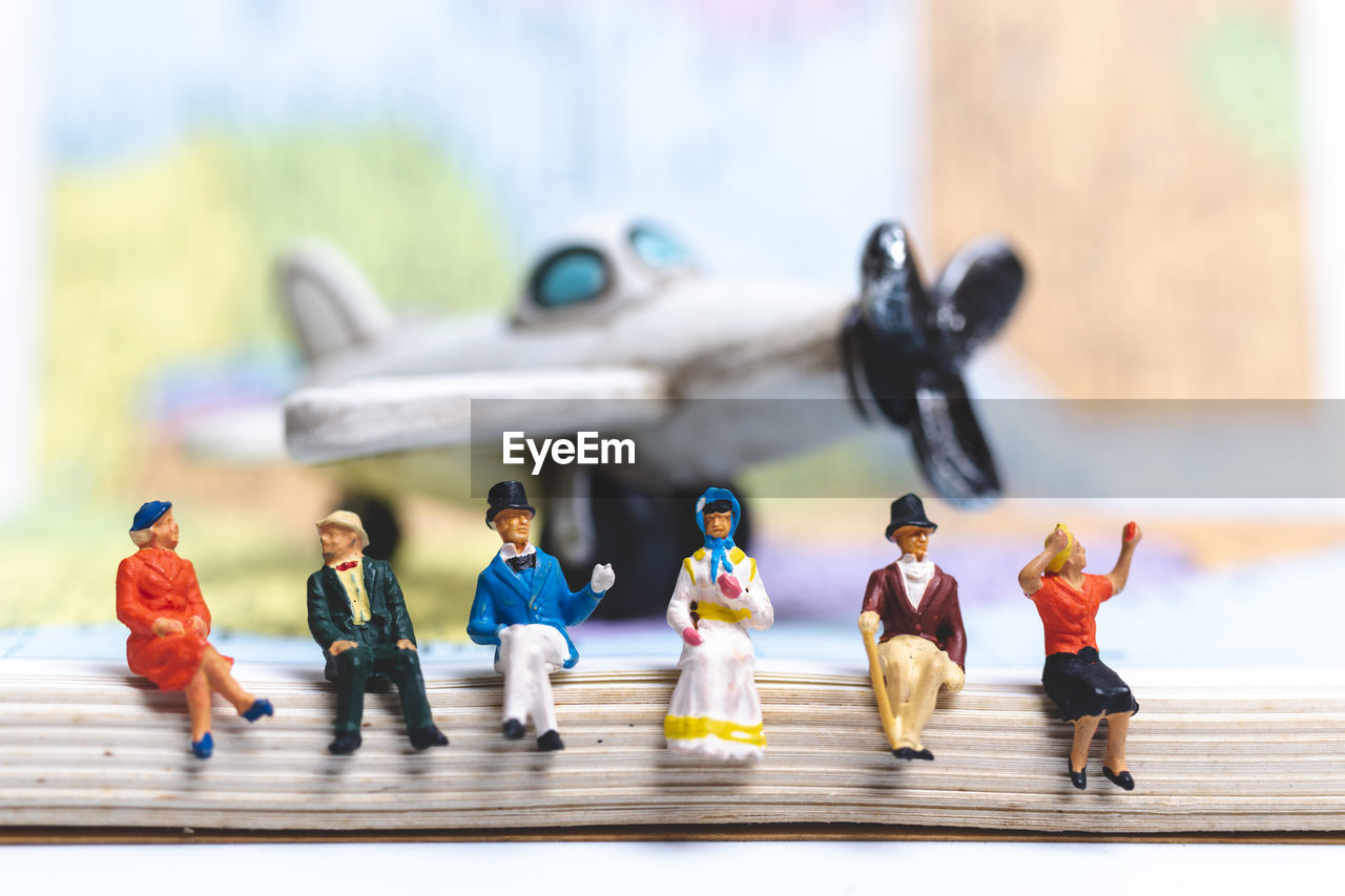 High angle view of figurines on book against toy airplane on table