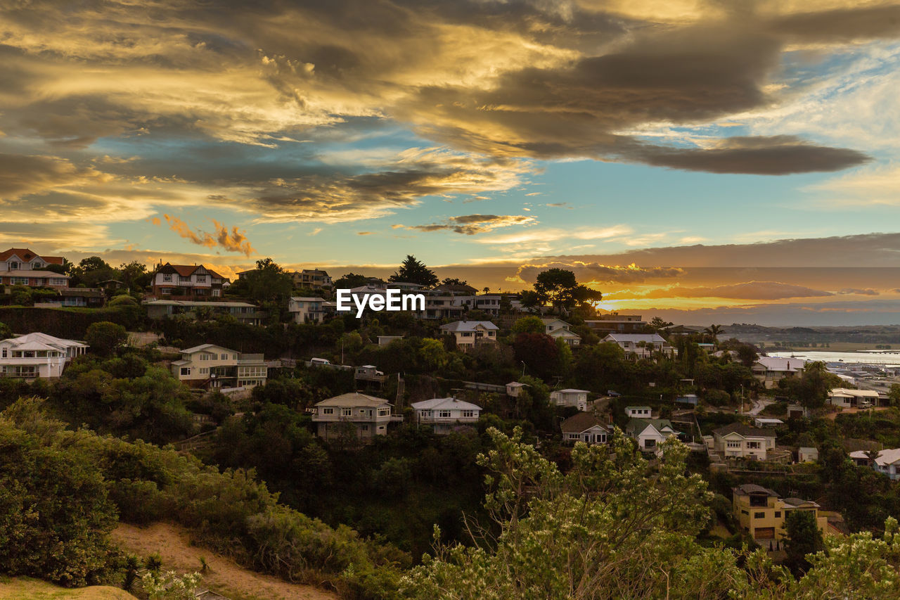architecture, building exterior, built structure, residential district, residential building, house, cloud - sky, sky, no people, outdoors, sunset, community, cityscape, spirituality, town, city, nature, travel destinations, tree, day, mountain