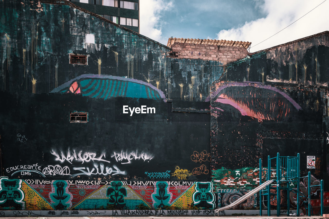 architecture, built structure, building exterior, graffiti, creativity, city, art and craft, multi colored, transportation, water, text, cloud - sky, street art, no people, building, day, sky, mode of transportation, nature, canal, mural