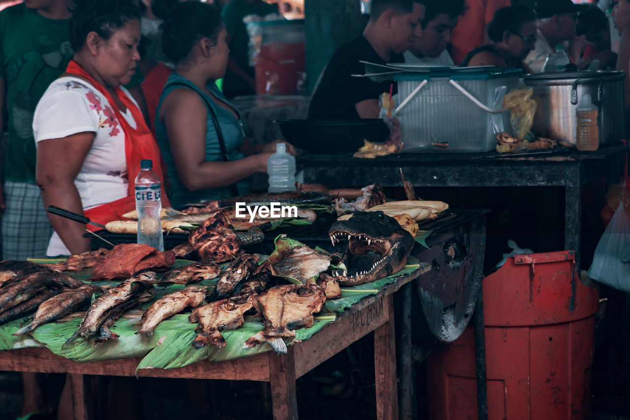 food, food and drink, meat, real people, men, freshness, barbecue, barbecue grill, people, preparation, occupation, grilled, indoors, seafood, preparing food, heat - temperature, incidental people, wellbeing, group of people, business, street food