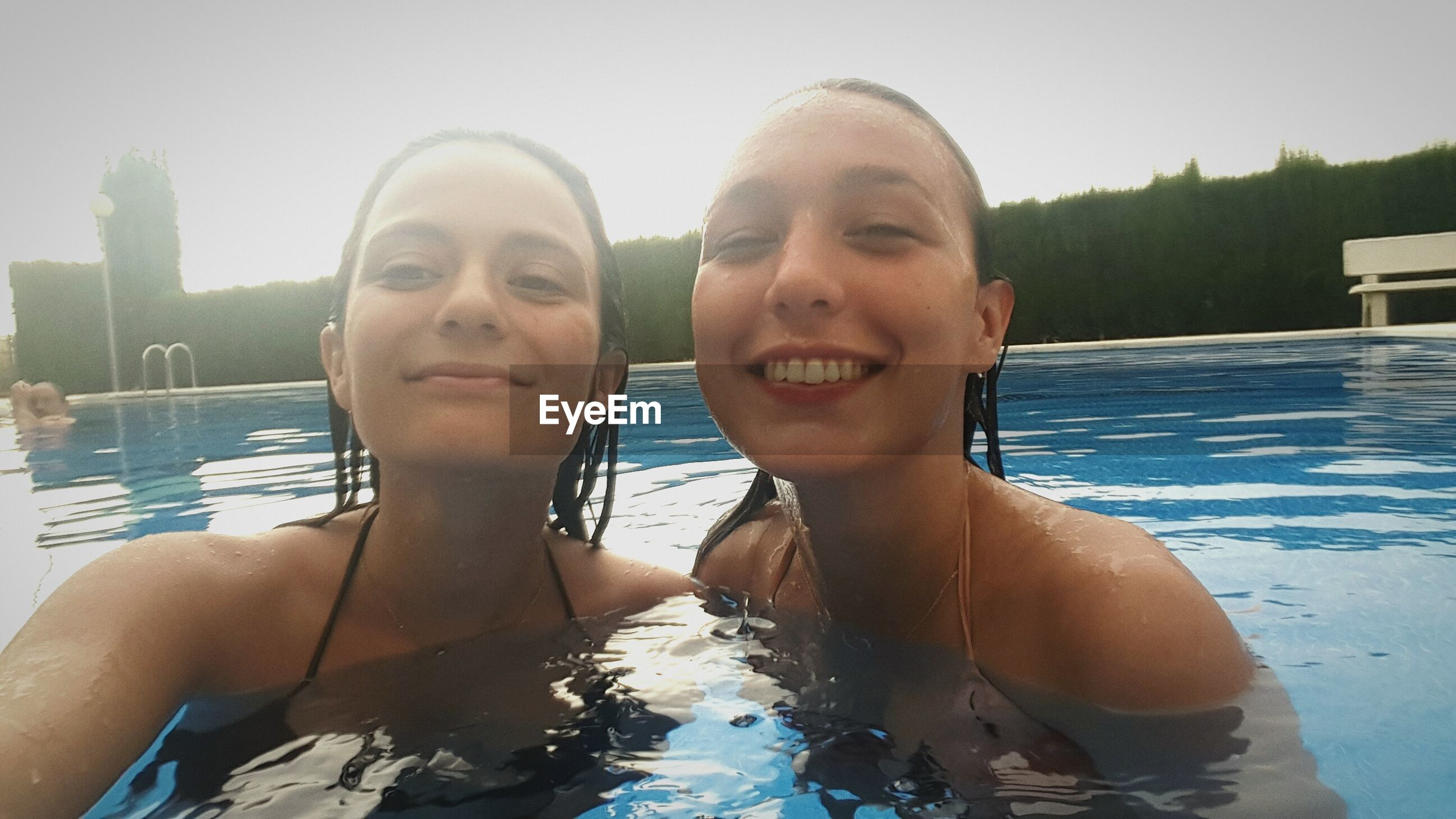 water, swimming pool, leisure activity, real people, togetherness, two people, day, young women, outdoors, lifestyles, vacations, looking at camera, young adult, headshot, smiling, sunlight, happiness, swimming, summer, portrait, bonding, sky, nature, childhood, close-up