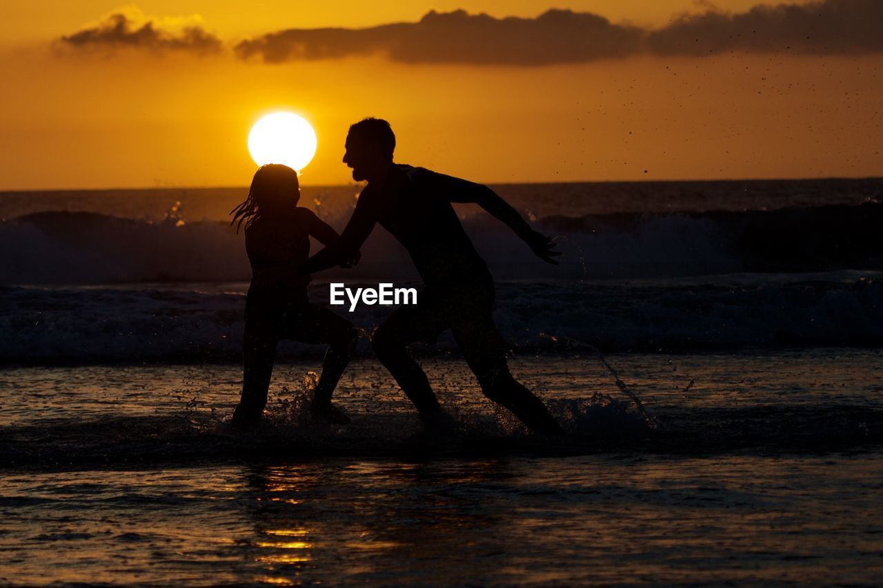 sunset, water, sky, two people, sea, togetherness, land, orange color, real people, beach, leisure activity, beauty in nature, nature, silhouette, men, lifestyles, bonding, scenics - nature, women, sun, horizon over water, positive emotion, outdoors, couple - relationship