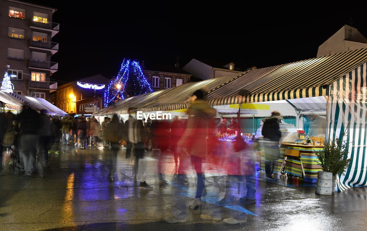 night, illuminated, architecture, city, building exterior, built structure, real people, motion, blurred motion, water, reflection, street, group of people, wet, transportation, city life, women, nature, sky, rain, outdoors, rainy season