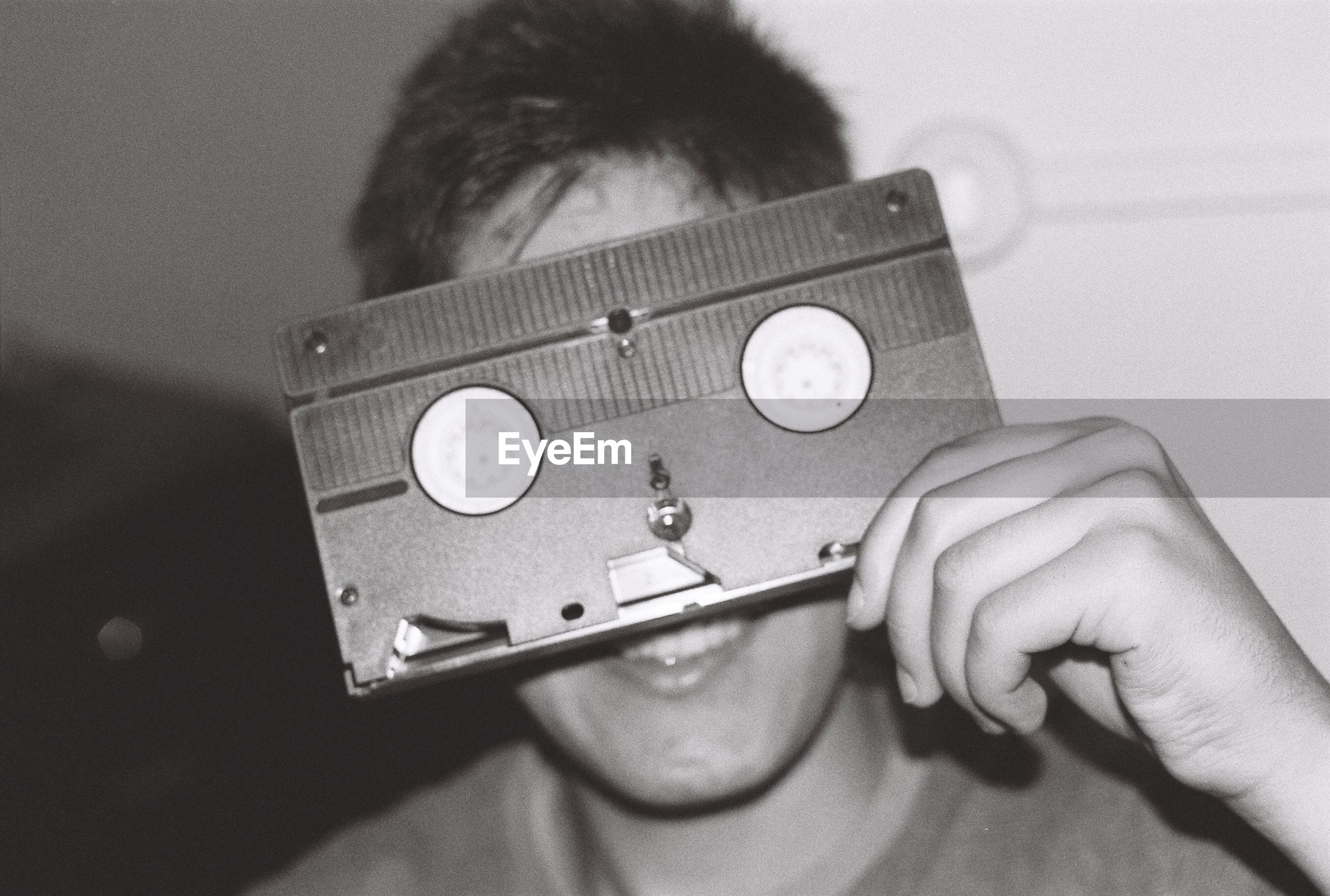 Close-up of boy holding audio cassette against face while sitting at home