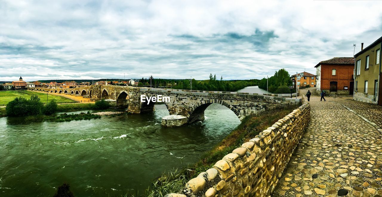 architecture, built structure, water, bridge - man made structure, sky, connection, building exterior, river, incidental people, cloud - sky, outdoors, arch, day, nature, travel destinations, tree