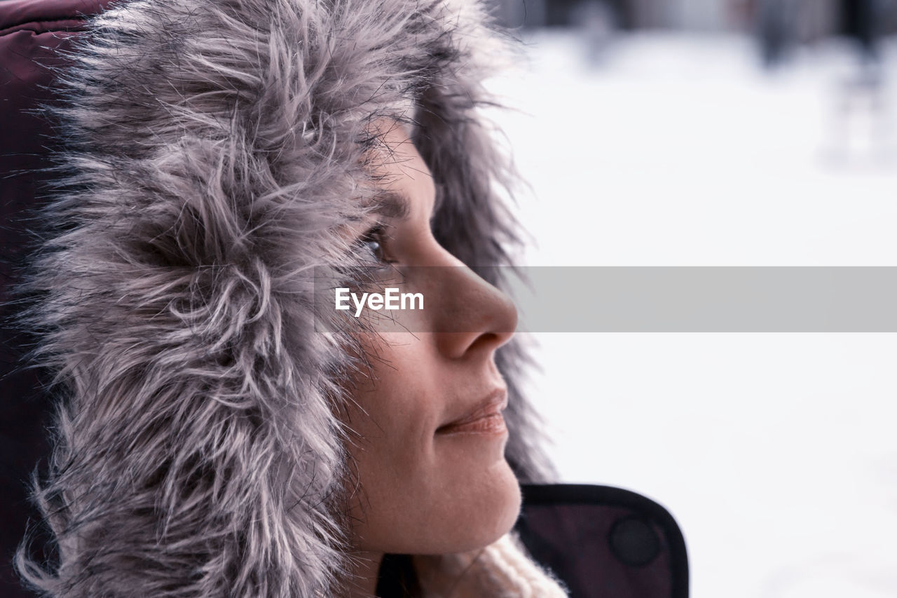 headshot, winter, one person, portrait, cold temperature, real people, focus on foreground, close-up, fur, warm clothing, lifestyles, leisure activity, looking away, looking, snow, day, clothing, fur hat, contemplation, hood - clothing