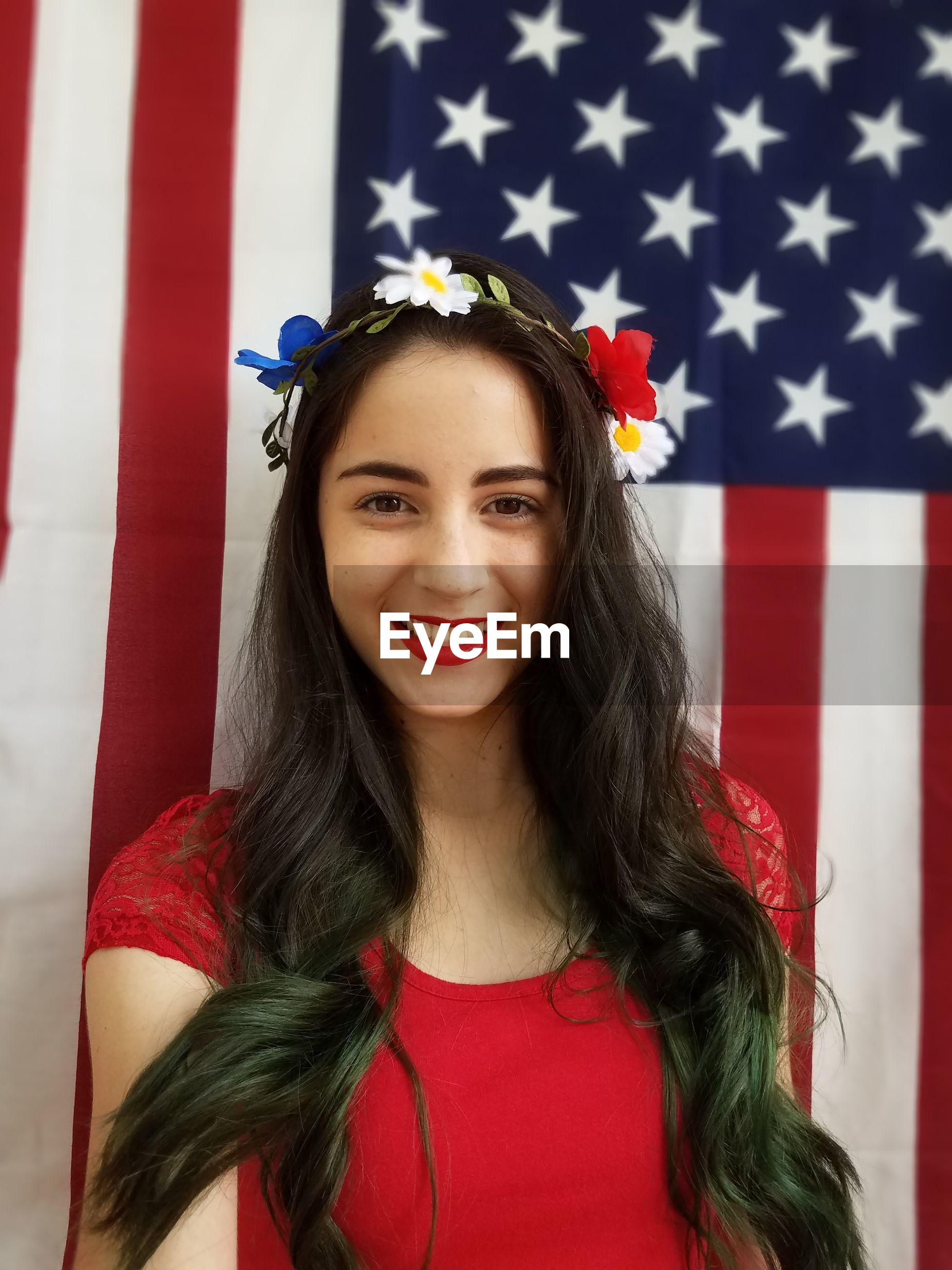 Portrait of beautiful young woman with long black hair against american flag