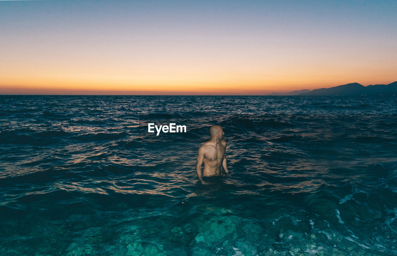 Shirtless Man Standing In Sea Against Clear Sky At Night