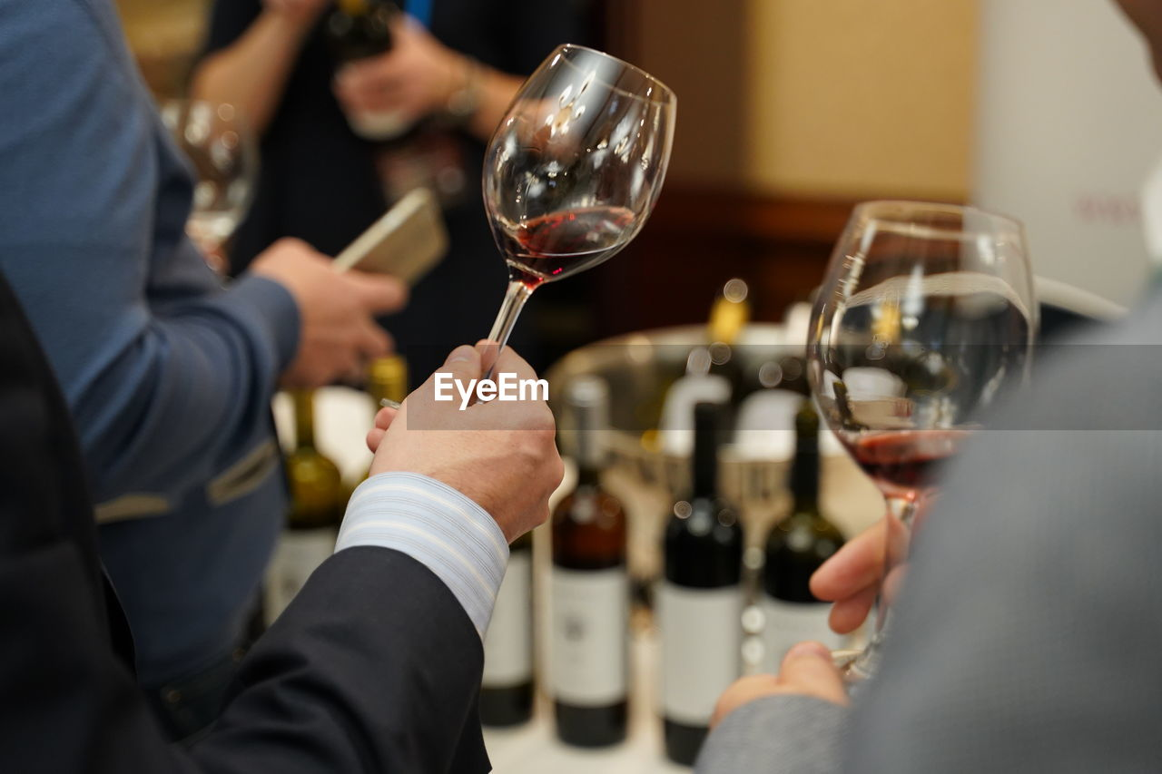 Midsection Of Men Holding Wineglasses In Party