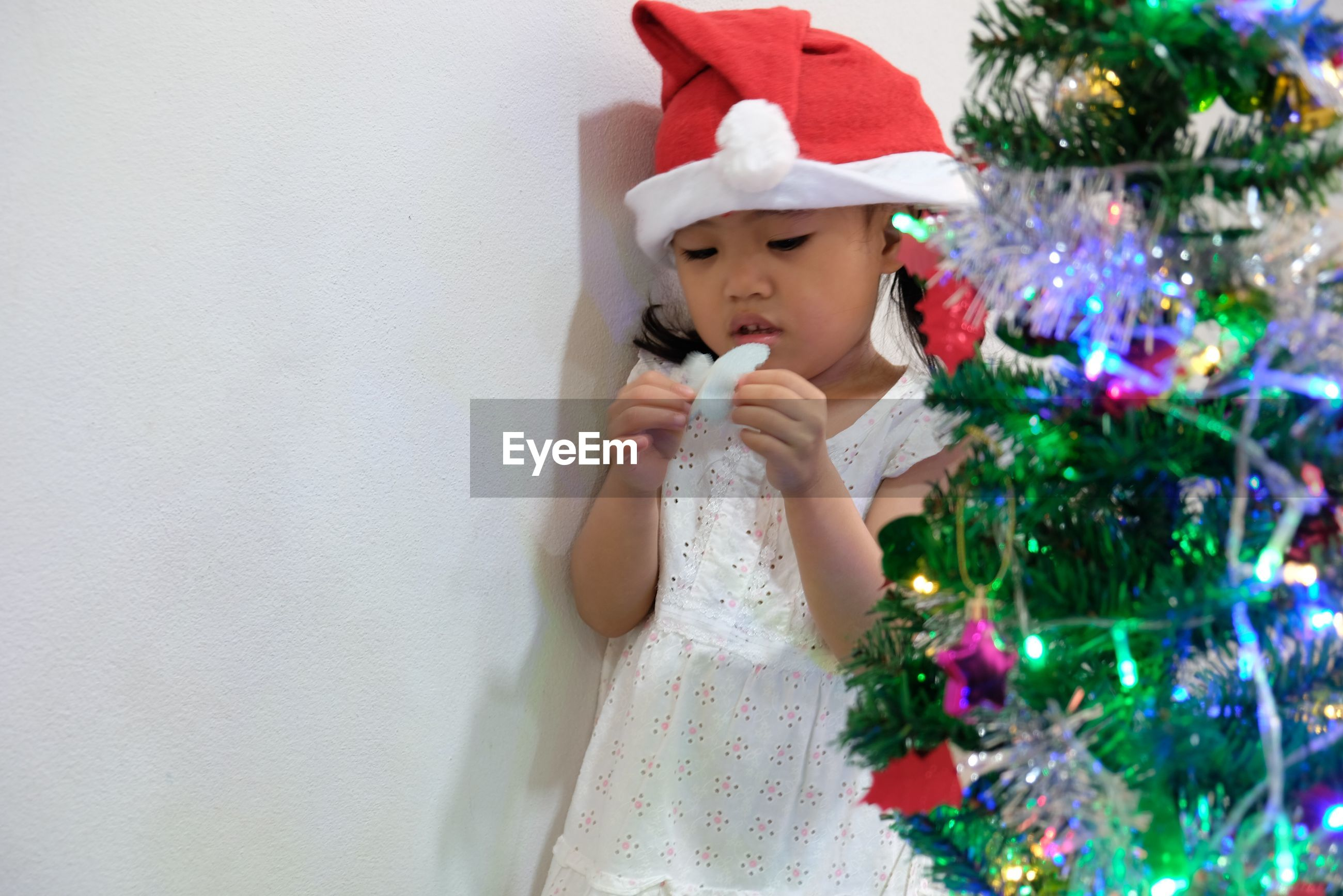 Cute girl standing by christmas tree at home