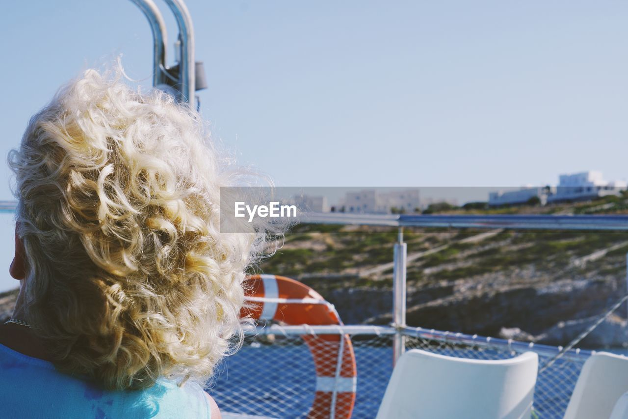 Rear View Of Boy On Boat Against Sky