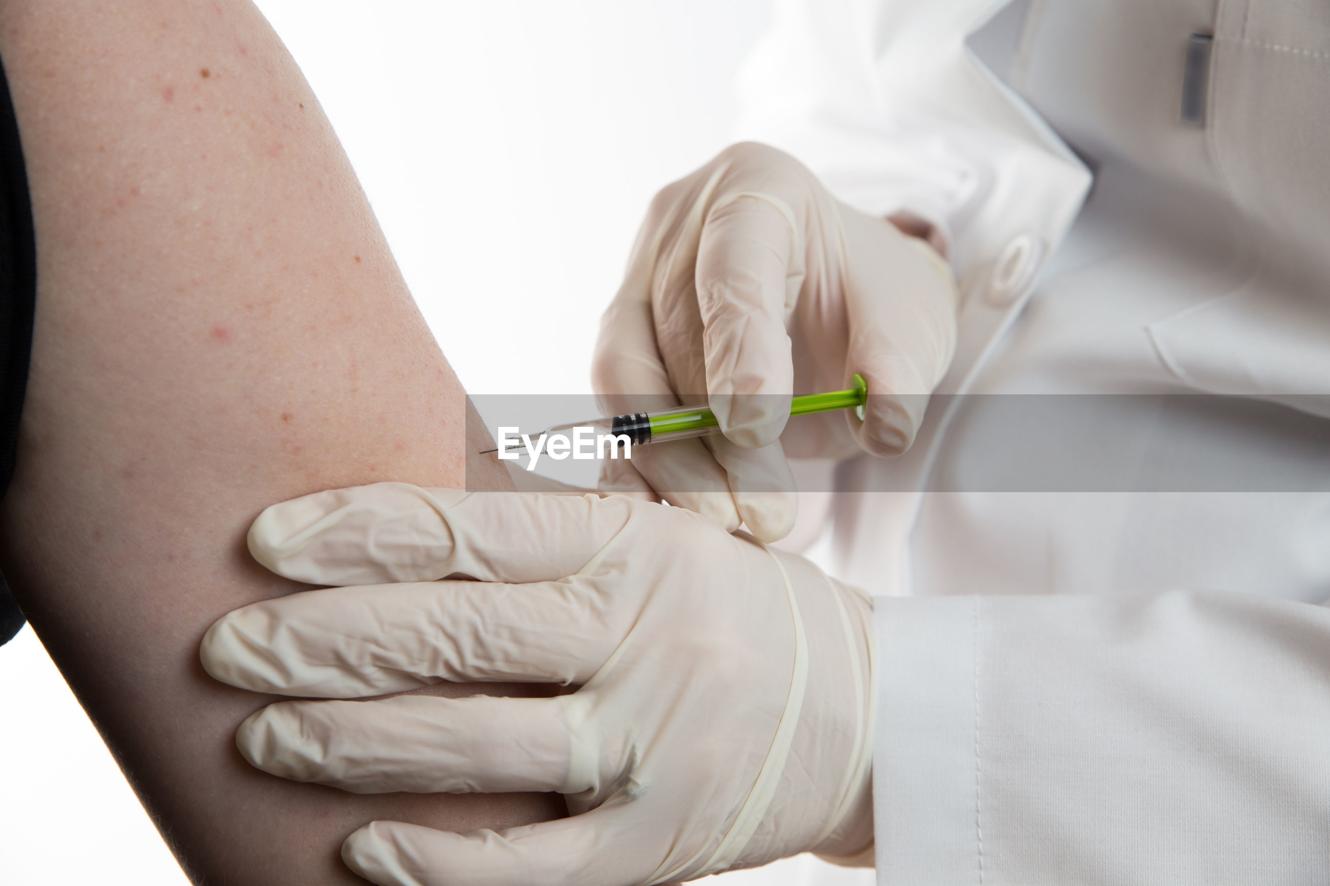 Midsection of doctor injecting syringe to patient against white background
