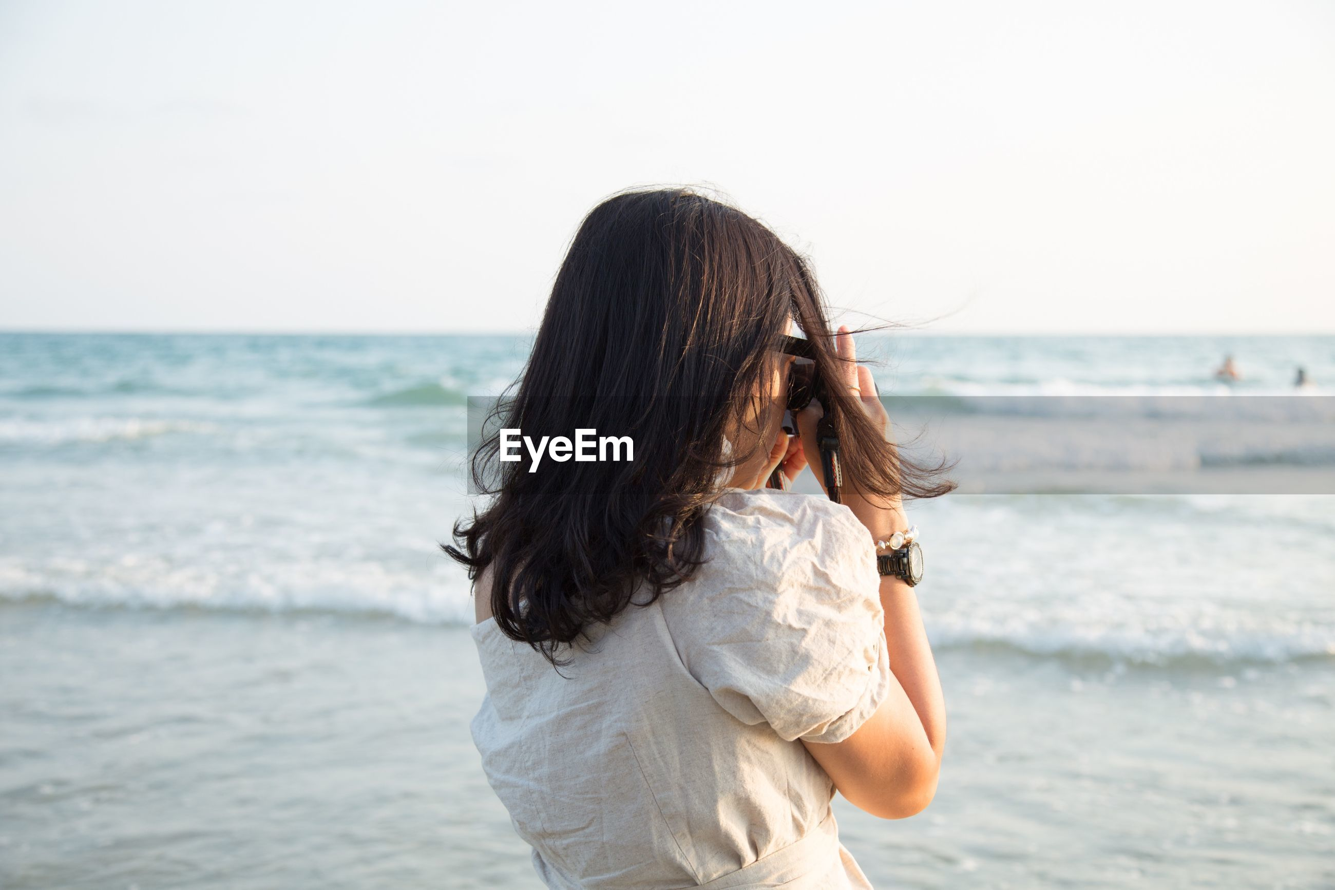 Woman photographing while standing at beach against sky