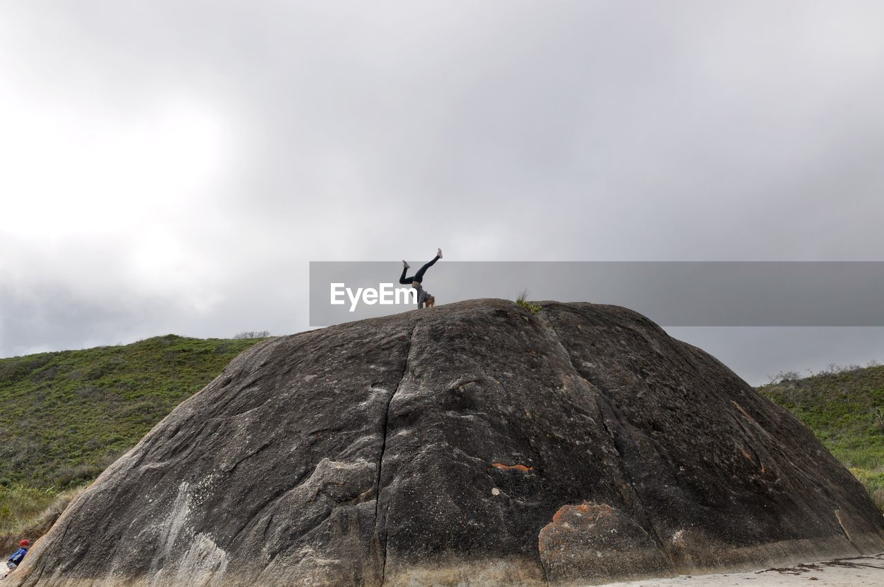 Woman doing handstand on rock formation against sky