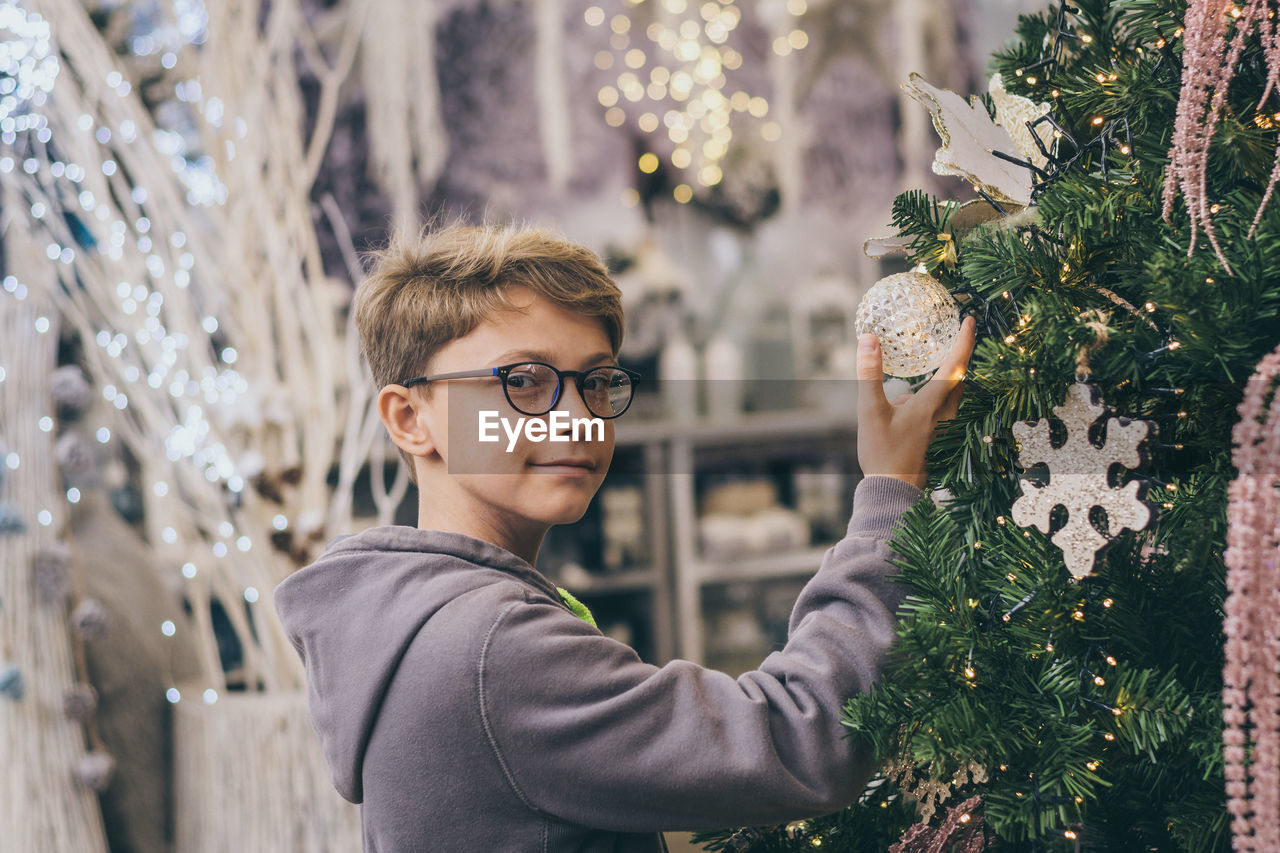 Portrait of boy standing by tree while touching christmas decoration at home