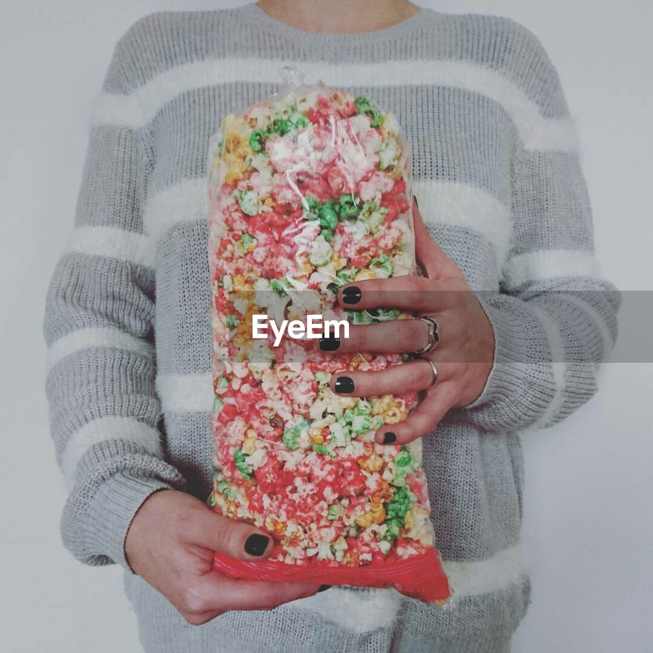 Midsection Of Woman Holding Bag Of Popcorn