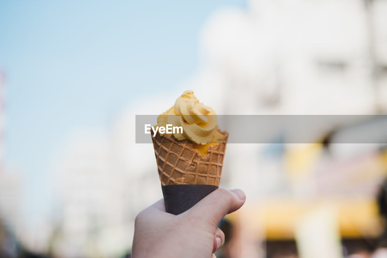 sweet food, sweet, frozen, ice cream, human hand, frozen food, hand, holding, dessert, indulgence, food and drink, food, temptation, one person, cone, human body part, ice cream cone, dairy product, focus on foreground, real people, finger, body part, outdoors, frozen sweet food, melting